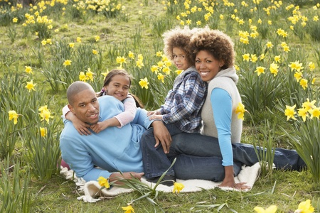 Familia que se relaja en campo de los narcisos de la primavera Foto de archivo - 65640937