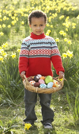 Boy On Easter Egg Hunt In Daffodil Field Stock Photo