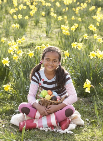 nine year old: Girl On Easter Egg Hunt In Daffodil Field Stock Photo