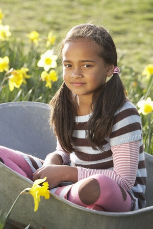nine year old: Girl On Sitting In Wheelbarrow In Daffodil Field