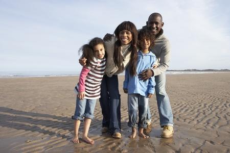 Family Walking On Winter Beach Stock Photo
