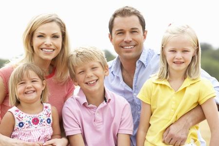 Familie sitzt auf Stroh-Ballen auf dem geernteten Gebiet Standard-Bild