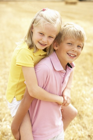 Portrait Of Boy And Girl In Summer Harvested Field Stock Photo