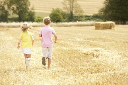 hay field: Children Running Through Summer Harvested Field
