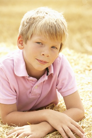 Portrait Of Boy Laying In Summer Harvested Field