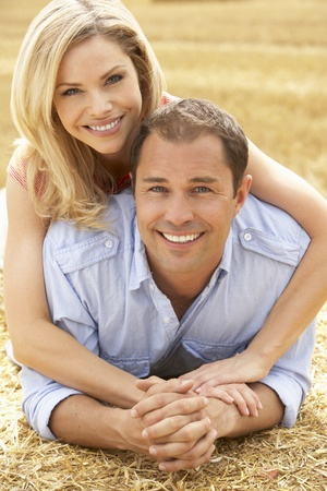 affections: Couple Relaxing In Summer Harvested Field Stock Photo