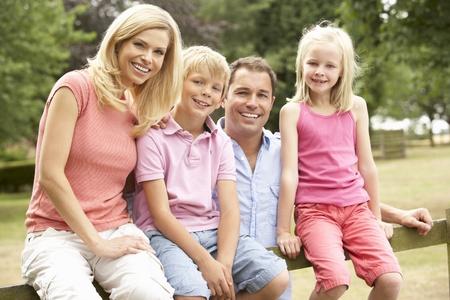 niños sentados: Retrato de la familia sentado en valla En Campo