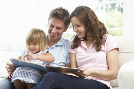 family sofa: Family Sitting On Sofa Reading Book At Home