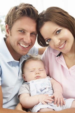 parents with baby: Close Up Of Parents Cuddling Newborn Baby Boy At Home Stock Photo