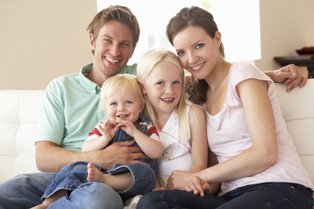 family sofa: Family Sitting On Sofa At Home Together Stock Photo