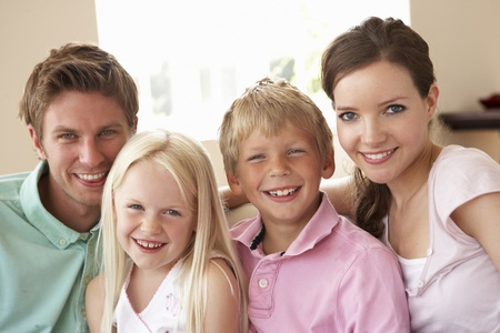 people laughing: Family Sitting On Sofa At Home Together Stock Photo