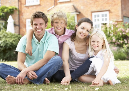 Family Sitting In Garden Together Stock Photo