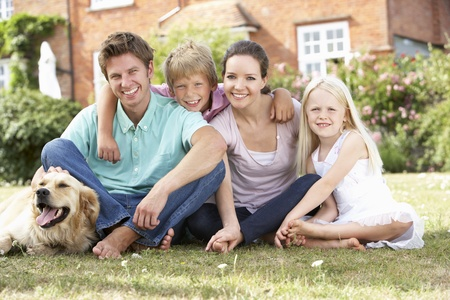 Familia que se sienta en jardín junto Foto de archivo