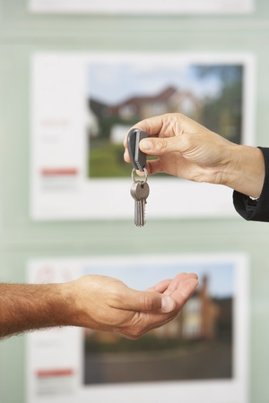 Close Up Of Estate Handing Over Keys Of New Home To Client Archivio Fotografico
