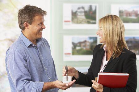 Weiblicher Zustand, der Schlüssel des neuen Hauses zum Kunden übergibt Standard-Bild - 85384426