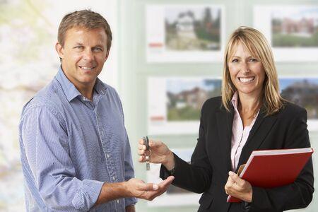 Weiblicher Zustand, der Schlüssel des neuen Hauses zum Kunden übergibt Standard-Bild - 85384422