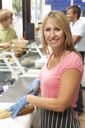 Woman Working Behind Counter In Café Stock Photo
