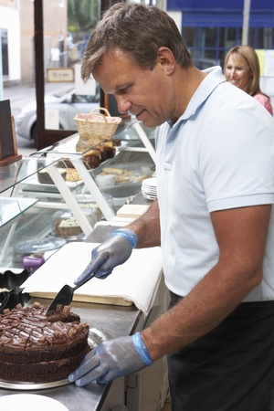 Man Working Behind Counter In Café Slicing Cake Stok Fotoğraf