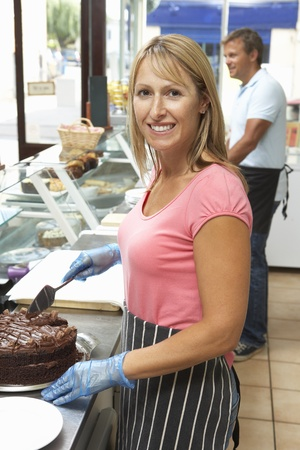 Woman Working Behind Counter In Café Slicing Cake