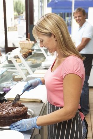 スライス ケーキのカフェでカウンターの後ろに働く女性