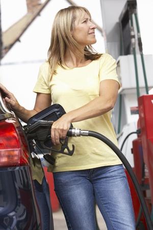 가솔린 역 디젤 자동차를 작성하는 여자 운전자의 세부 사항
