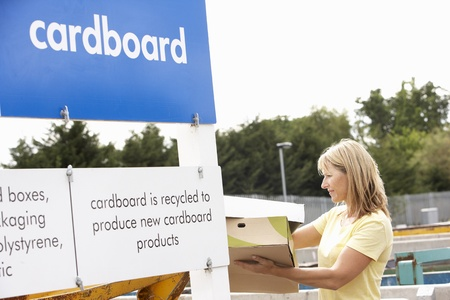 environmental issues: Woman At Recycling Centre Disposing Of Cardboard