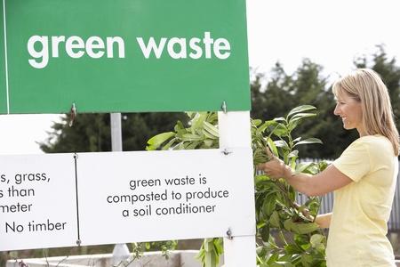 Man At Recycling Centre Disposing Of Garden Waste Stock Photo