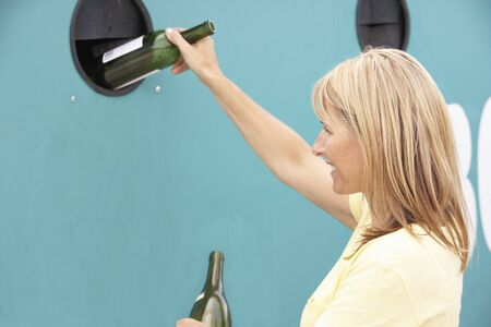 environmental issues: Woman At Recycling Centre Disposing Of Glass At Bottle Bank
