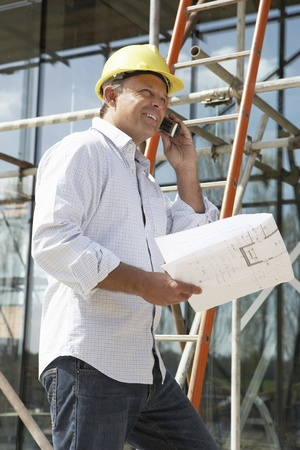 outside house: Architect With Plans Outside New Home Talking On Mobile Phone