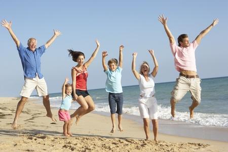 Portrait de famille de trois génération sur les vacances de plage sautant en l'air