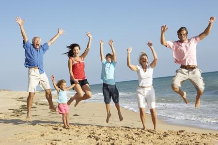 三世代家庭畫象跳躍在空氣的海灘假日的 版權商用圖片