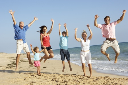Portrét tří generací rodiny na dovolenou na pláži skákání ve vzduchu