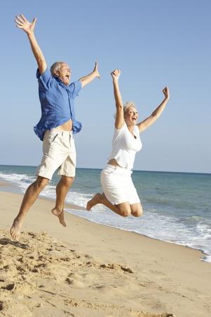 Pareja Senior disfrutando de vacaciones en la playa saltando en el aire