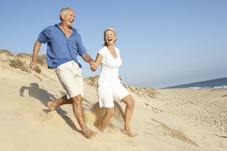모래 언덕을 실행하는 해변 휴가를 즐기는 수석 커플 스톡 콘텐츠