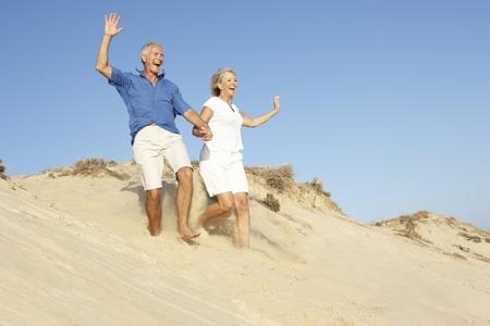 Senior Couple Enjoying Beach Holiday Running Down Dune Archivio Fotografico