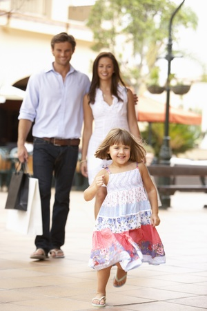 Young Family Enjoying Shopping Trip Together Stock Photo
