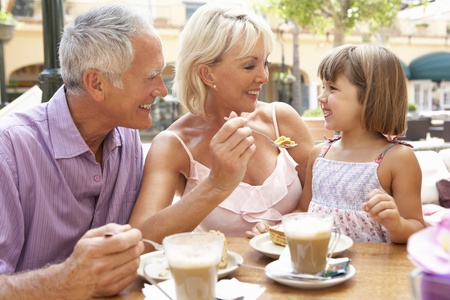 coffee and cake: Grandparents With Granddaughter Enjoying Coffee And Cake In Caf?
