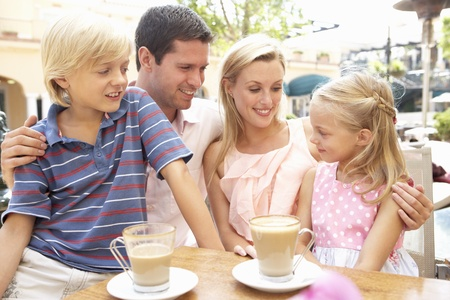 Young Family Enjoying Cup Of Coffee In Caf? Together Stock Photo