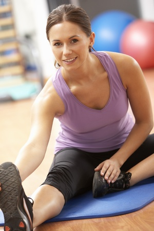 Caucasian woman: Woman Doing Stretching Exercises In Gym Stock Photo