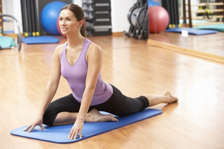 keeping fit: Woman Doing Stretching Exercises In Gym Stock Photo
