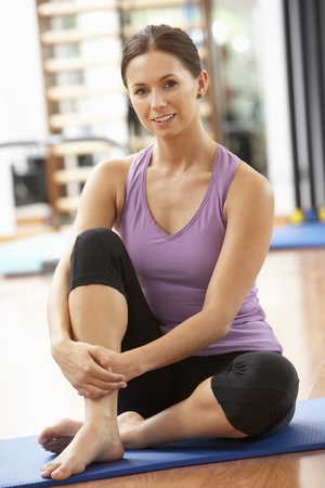 Woman Doing Stretching Exercises In Gym Stock Photo