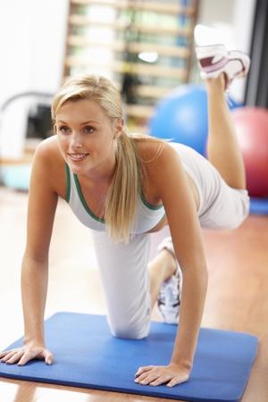 ジムでストレッチ体操を行う若い女性