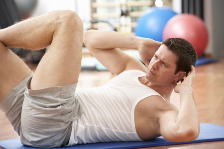 keeping fit: Man Doing Stretching Exercises In Gym Stock Photo