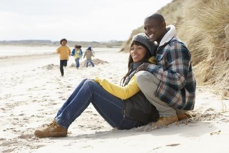 Family Having Fun On Winter Beach Stock Photo