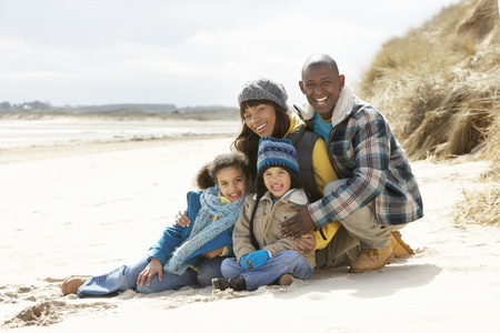 겨울 해변에 앉아있는 가족