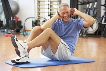 haciendo ejercicio: El hombre mayor que el hacer se sienta sube en gimnasia