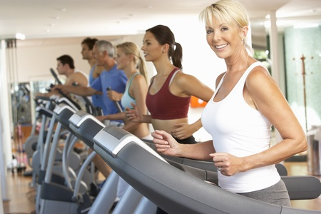 Senior Woman On Running Machine In Gym Imagens