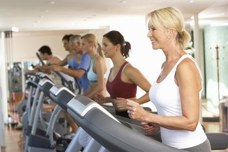 Senior Woman On Running Machine In Gym Stok Fotoğraf