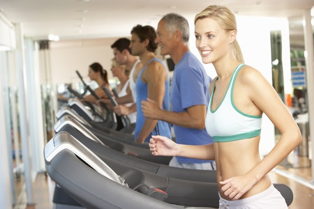 keeping fit: Woman On Running Machine In Gym Stock Photo