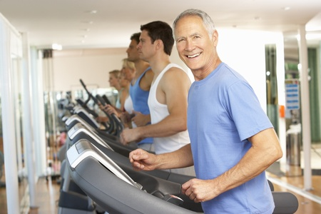 Senior Man On Running Machine In Gym
